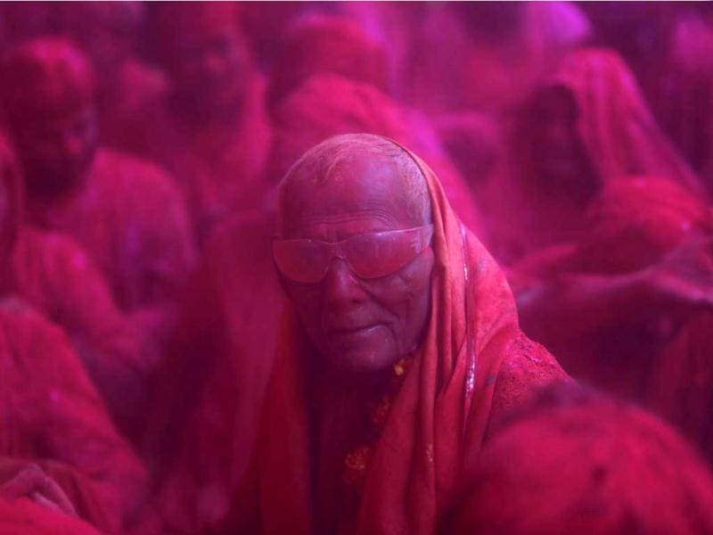A devotee looks on in a cloud of coloured powder inside a temple during Lathmar Holi at the village of Barsana in Uttar Pradesh. (Reuters)