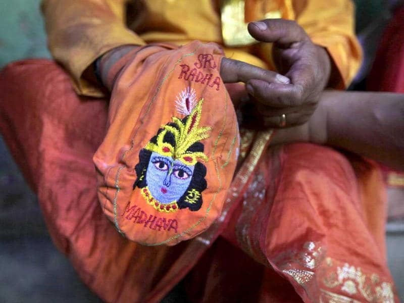 A priest prays holding a bag with an image of Krishna at the Ladali or Radha temple during the Lathmar Holy festival in Barsana. (AP)