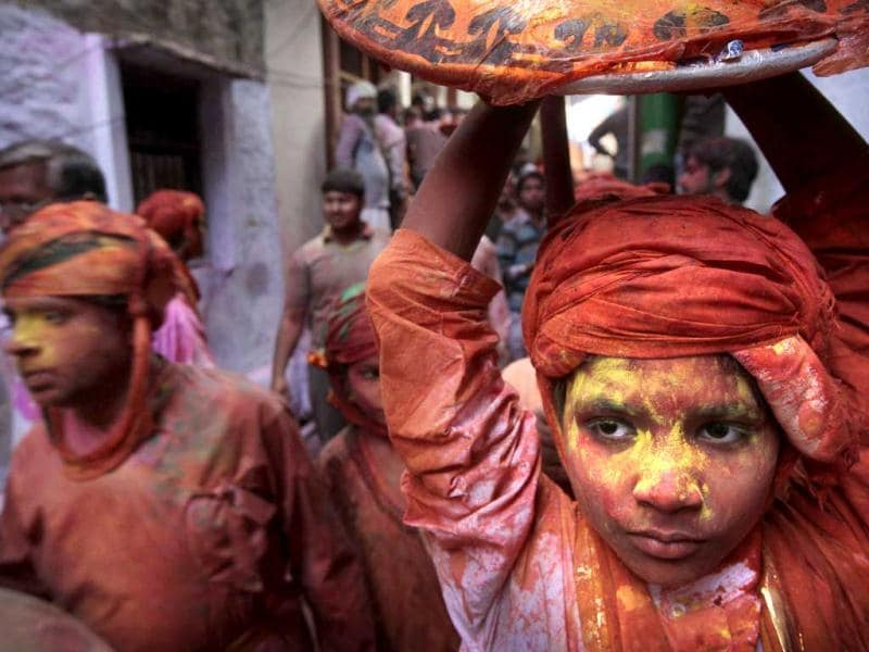 A young boy from Nandgaon soaked in water and colors arrives in Barsana village during the Lathmar Holy festival in Barsana. (AP)