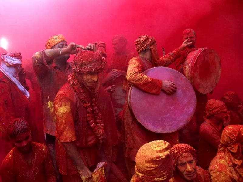 Members of a band stand in a cloud of coloured powder inside a temple during Lathmar Holi at the village of Barsana in Uttar Pradesh. (Reuters)