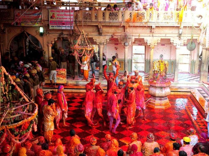 Devotees dance covered in coloured powder at the Radha Rani temple during the Lathmar Holi festival in Barsana. (AFP)