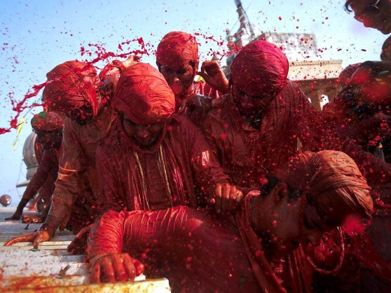 Devotees throw coloured water at each other at a temple during Lathmar Holi at the village of Barsana in Uttar Pradesh. (Reuters)