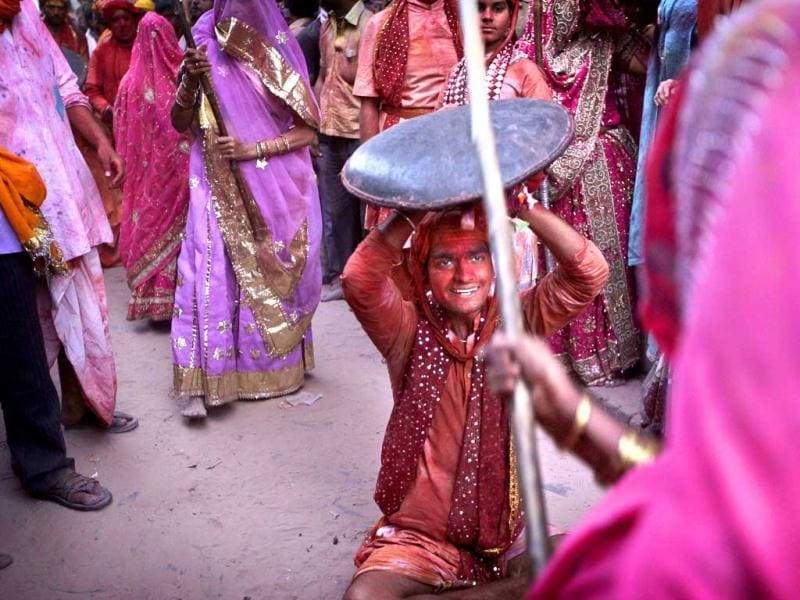 A woman from Barsana village hits a villager from Nandgaon with a wooden stick during the Lathmar Holy festival at the hometown of Radha, in Barsana. (AP)