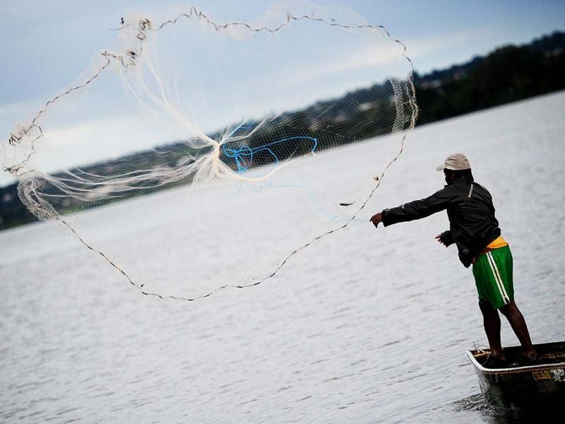 A fisherman throws a fishing net into Paranoa Lake, in Brasilia on World Water Day. (AFP)