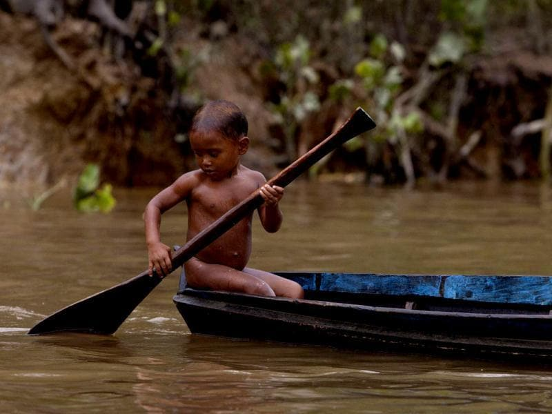 A child paddles in the Aura River, contaminated by the Aura garbage dump, near the mouth of the Amazon in Ananindeua. (Reuters)