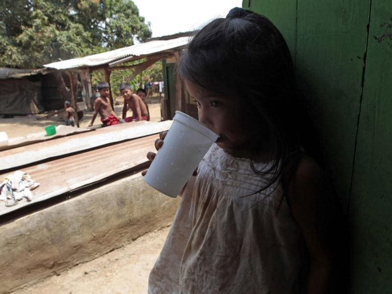 A girl drinks water at the front door of her house at the indigenous community of Pacayita in Masaya. (Reuters)