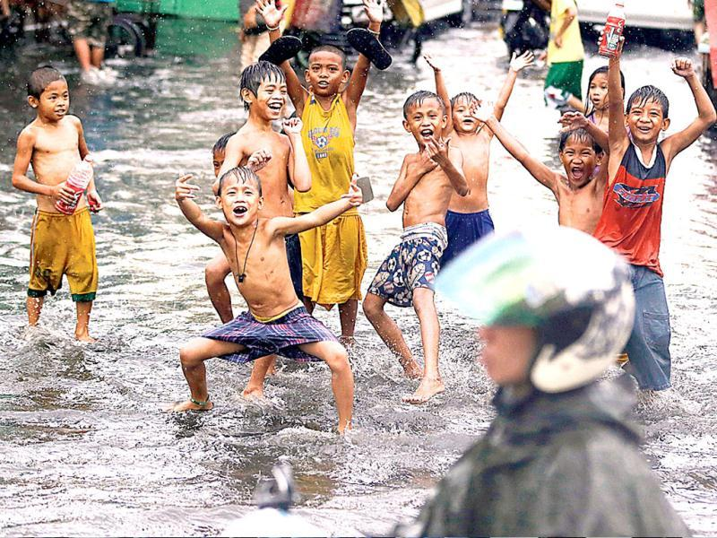 Children play at a flooded street following a sudden downpour as the world marks World Water Day in Manila, Philippines. (AP)
