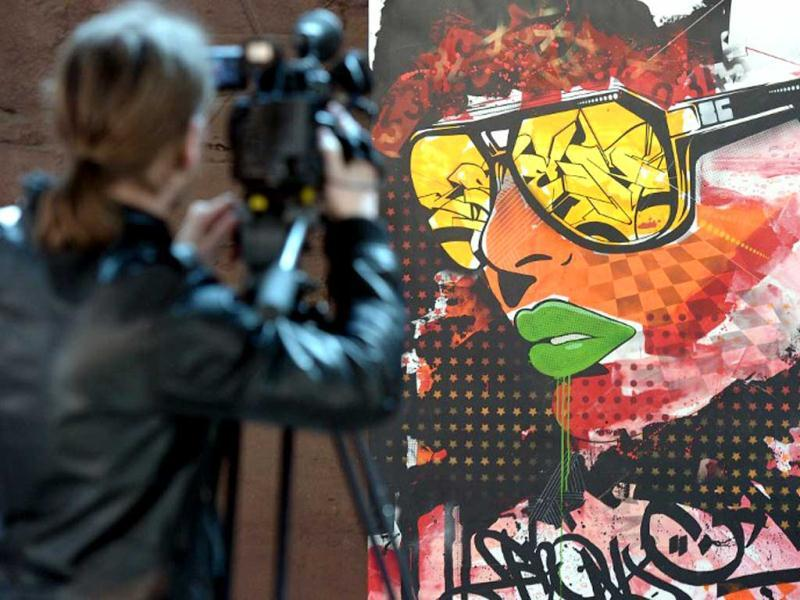 A cameraman films a painting by US graffiti an artist at the 'Urban Art Graffiti 21' exhibtion at the World Cultural Heritage Site at the Volklingen Ironworks. (AFP Photo)