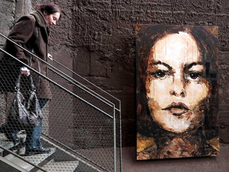 A visitor walks by a painting of German street artist El Bocho at the