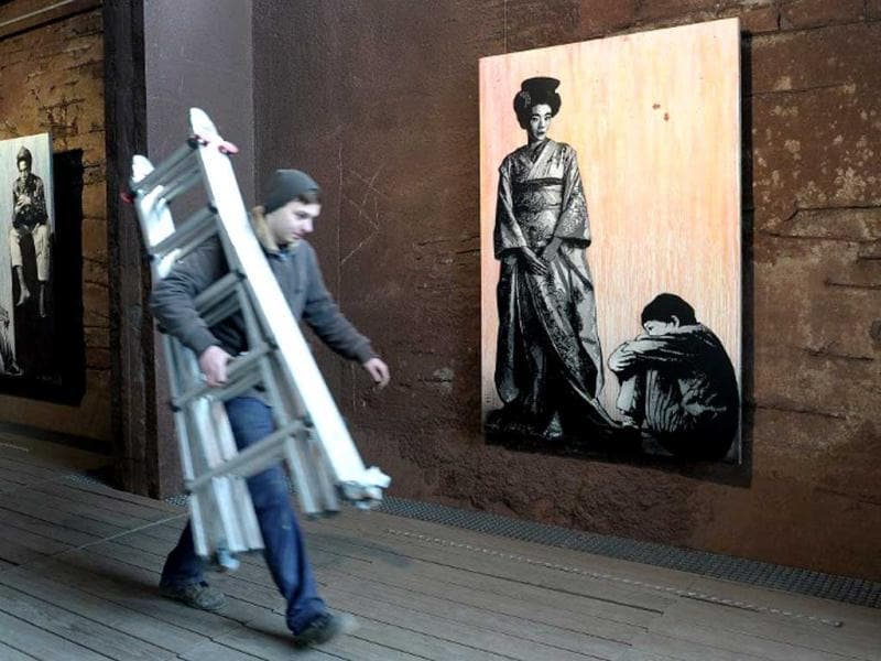 A man passes by a painting by French street artist Jef Aerosol at the