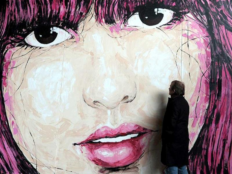 A visitor looks at a mural by German street artist El Bocho at the
