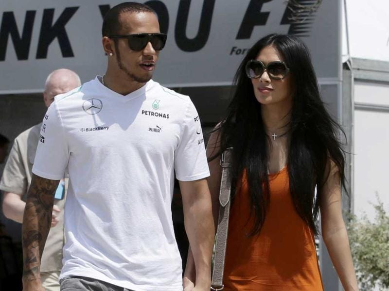 Mercedes Formula One driver Hamilton walks with girlfriend Scherzinger in the paddock before the start of the third practice session of the Malaysian F1 Grand Prix at Sepang International Circuit outside Kuala Lumpur. (Reuters)