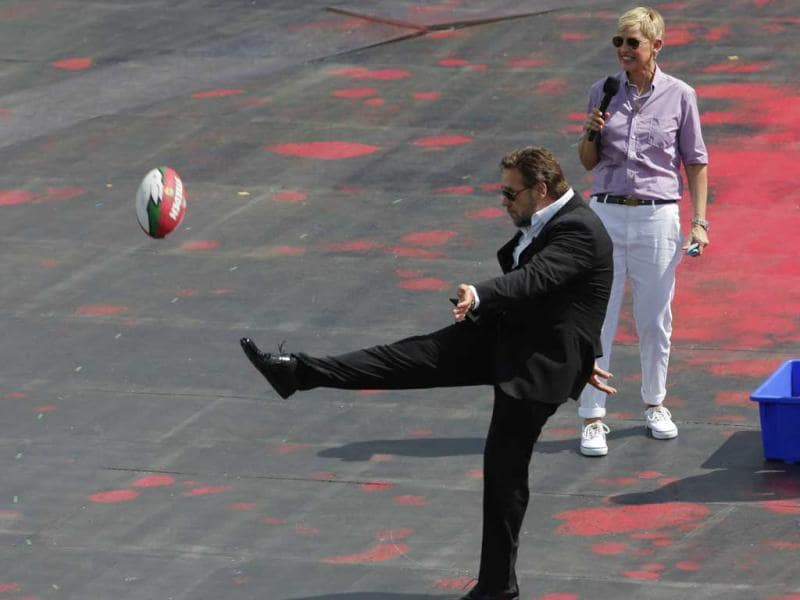 US talk show host Ellen DeGeneres watches as actor Russell Crowe kicks a football into the crowd during a recording for Ellen's show in Sydney. (AP)