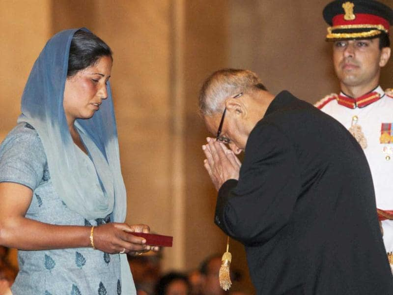 President Pranab Mukherjee after presenting Shaurya Chakra to the widow of Naik Anil Kumar during the Defence Investiture Ceremony at Rashtrapati Bhavan in New Delhi. (PTI)