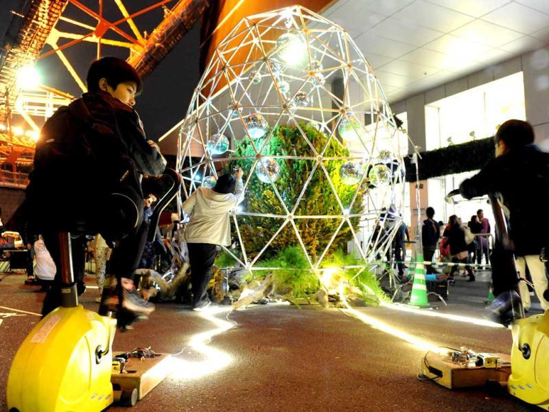 Tokyo residents pedal to generate electricity to light LED lights of the mirror ball inside an art installation during the 7th annual Earth Hour global warming campaign in Tokyo. AFP