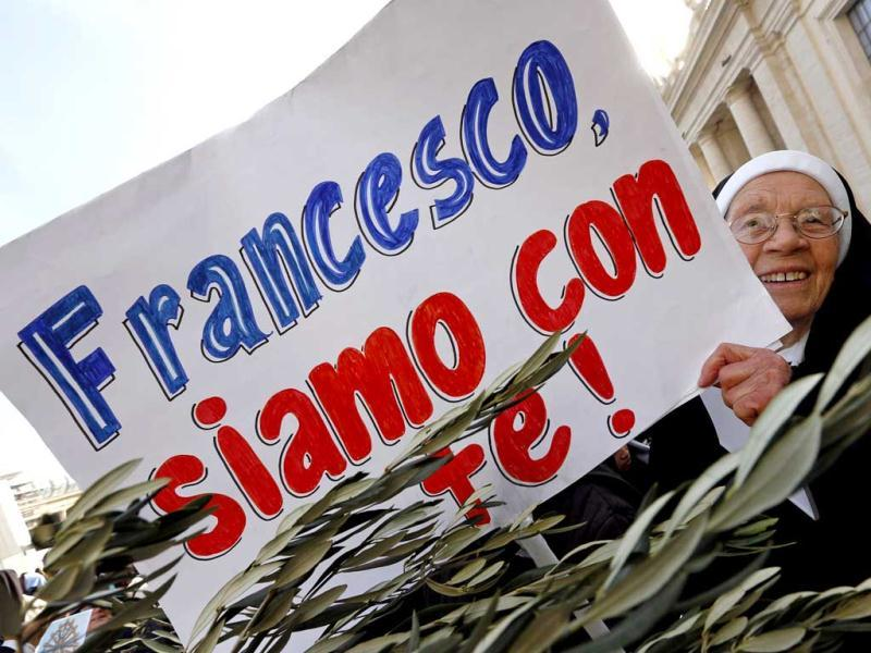A nun holds a placard as she waits for Pope Francis at the Palm Sunday mass at Saint Peter's Square. The placard reads,