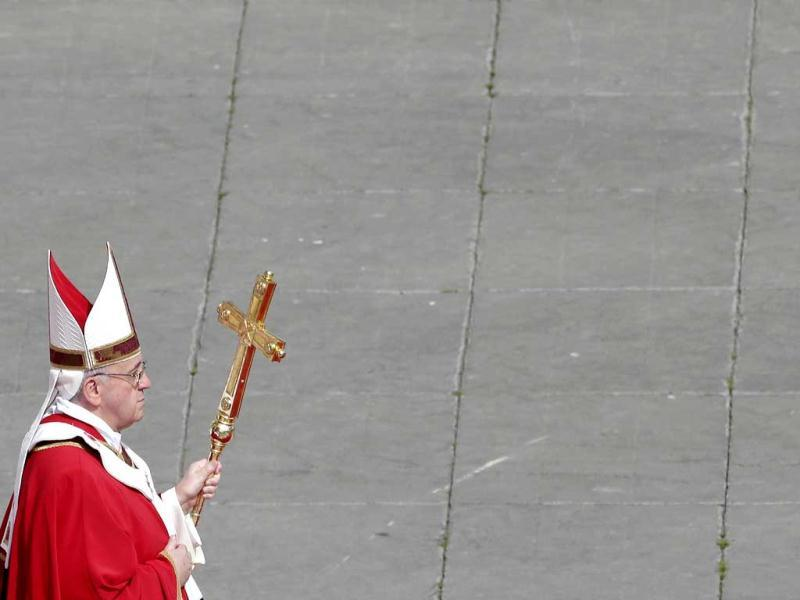 Pope Francis walks with his papal cross during the Palm Sunday mass at Saint Peter's Square at the Vatican. Reuters