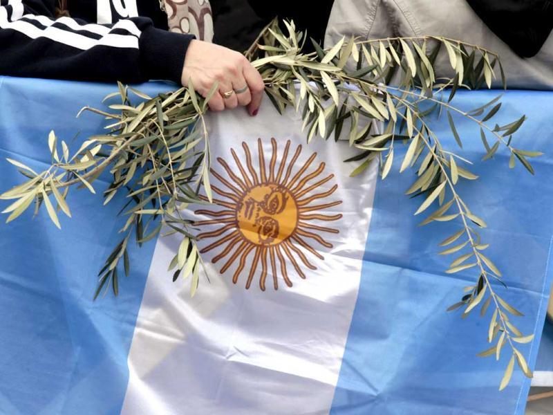 A faithful holds olive branches and an Argentine flag as Pope Francis celebrates his first Palm Sunday Mass in St. Peter's Square at the Vatican. AP
