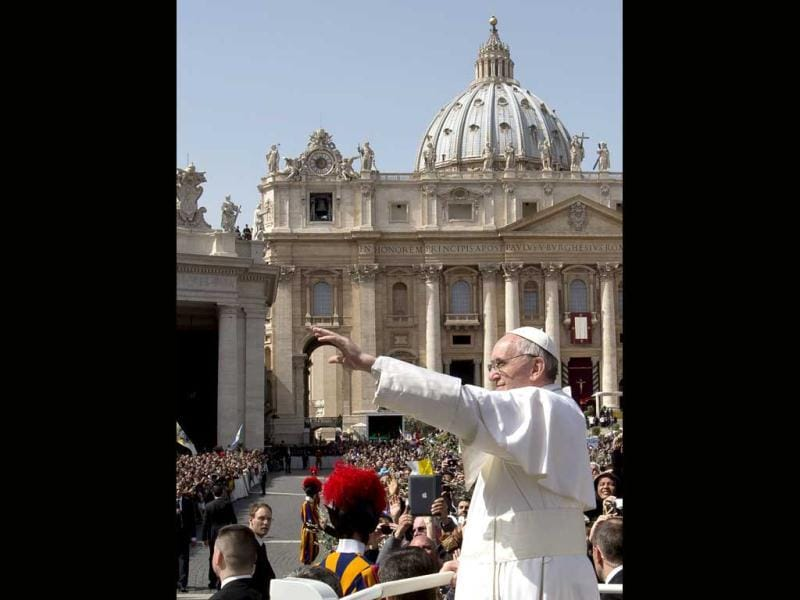Pope Francis waves at a cheering crowd as he wades through St. Peter's Square at the Vatican on Palm Sunday. AP