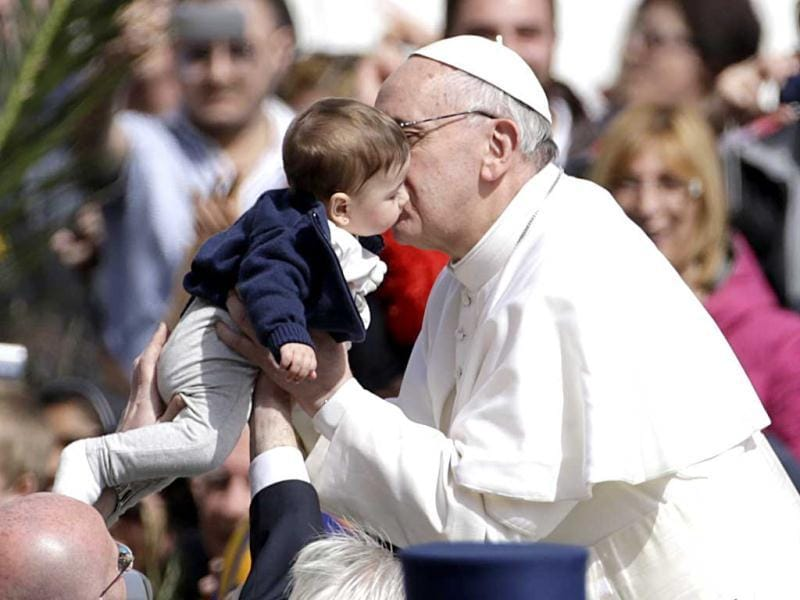 Pope Francis kisses a child as he leaves after celebrating his first Palm Sunday Mass, in St. Peter's Square. AP