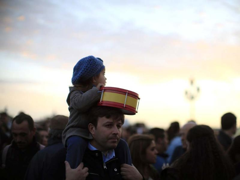 A girl sits on the shoulders of a man as they watch the procession of