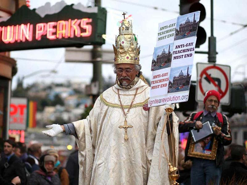 A same-sex marriage supporter dressed as the pope holds a sign during a rally in support of marriage equality in San Francisco, California. AFP