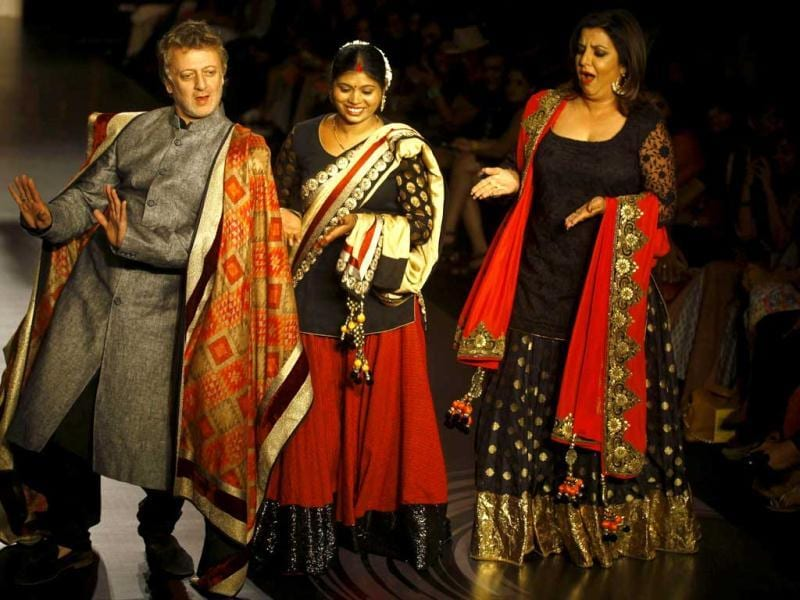 Designer Rohit Bal, left, and Bollywood Director Farah Khan, right, along with social activist Sanjana Sanjay Khedekar display creations by Vikram Phadnis during the Lakme Fashion Week in Mumbai, India. (AP Photo)