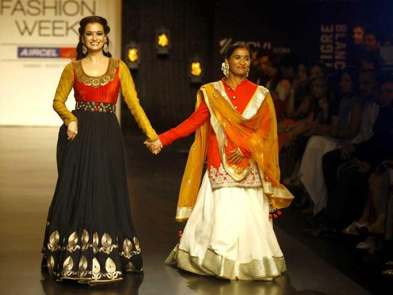 Dia Mirza, left, along with social activist Rohini Valvatkar displays creations by Vikram Phadnis during the Lakme Fashion Week in Mumbai, India. (AP Photo)