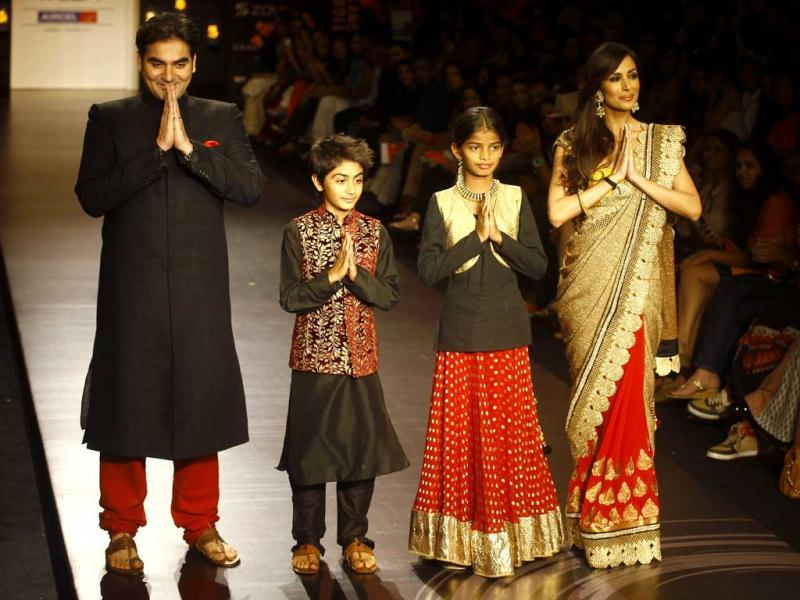 Arbaaz Khan, left, his son Arhaan Khan and wife Malaika Arora Khan, right, along with young environmental activist Diksha Pawar display creations by Vikram Phadnis during the Lakme Fashion Week in Mumbai, India. (AP Photo)