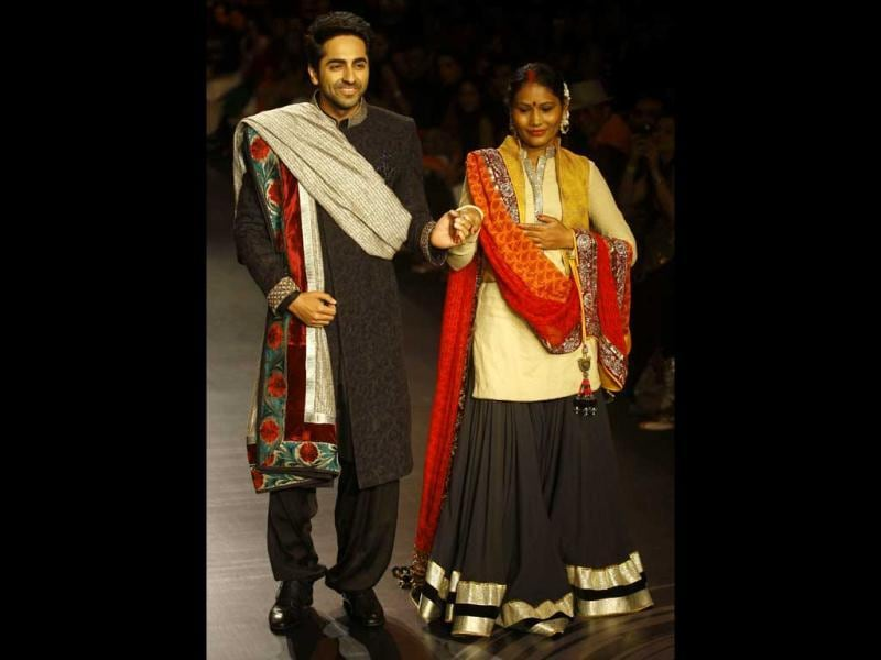 Ayushmann Khurrana, left, along with health worker and activist Sunita Sutar displays creations by Vikram Phadnis during the Lakme Fashion Week in Mumbai. (AP Photo)