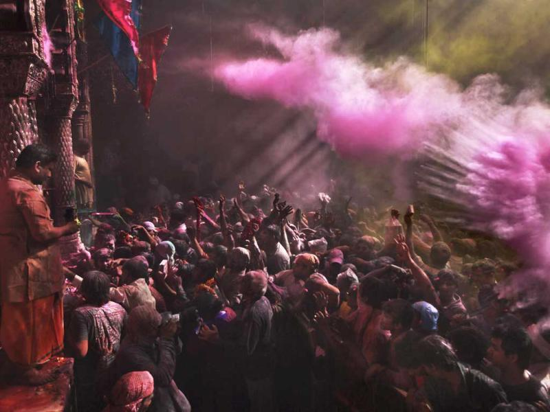 Hindu devotees throw coloured powder on each other inside Banke Bihari temple during Holi festival celebrations in Vrindavan. Holi, the festival of colors celebrates the arrival of spring among other things. AP