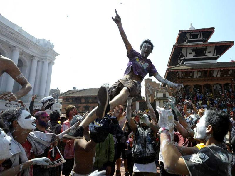 A Nepalese reveller is tossed into the air during celebrations of the Holi festival in Kathmandu. AFP