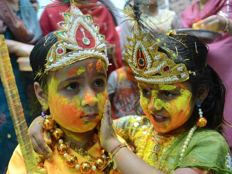 Children dressed as Lord Krishna and Radha play with coloured powder during a Holi celebration at a temple in Amritsar. AFP