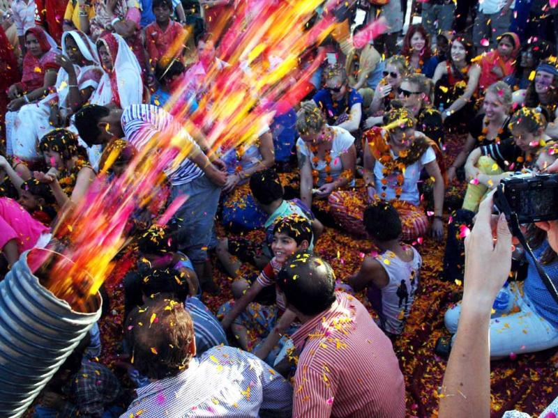 Foreign tourists participating in a Holi celebration near Clock Tower in Jodhpur. UNI