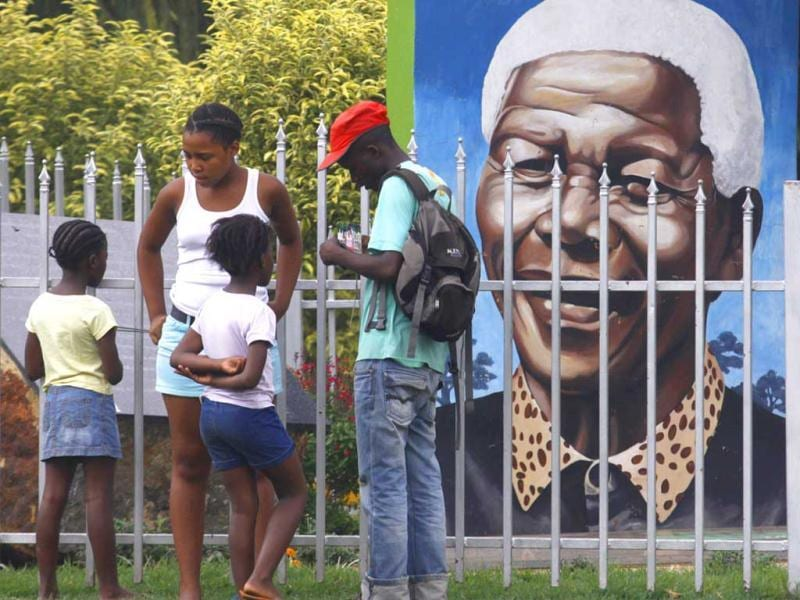 Visitors gather in front of a portrait of former president Nelson Mandela, in a park in Soweto, South Africa. Mandela, has become increasingly frail in recent years and has been hospitalised recently. AP/Denis Farrell