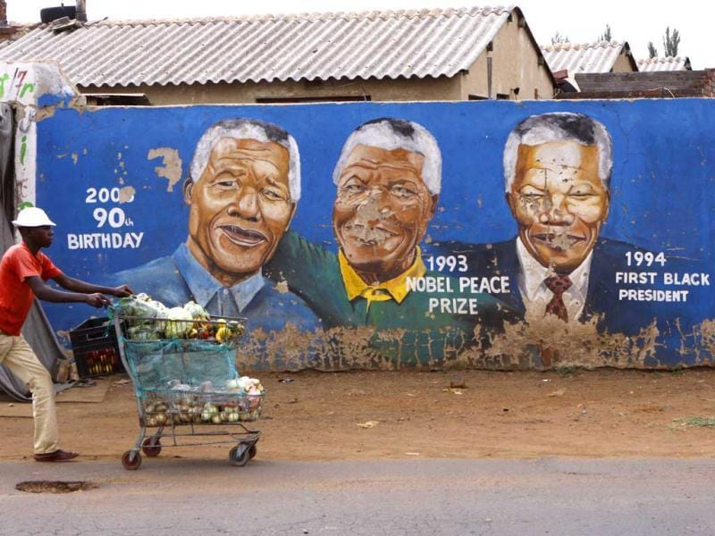 A hawker passes by portraits of former president Nelson Mandela depicted in various stages of his life in a Soweto, South Africa. AP/Denis Farrell