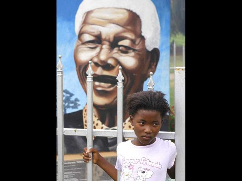 A child stands in front of Nelson Mandela's portrait in a park in Soweto, South Africa. AP/Denis Farrell