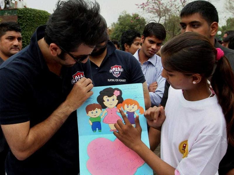 Ranbir Kapoor receives a painting during a charity football match in New Delhi on Thursday. PTI Photo