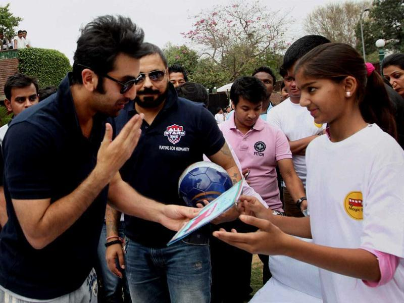 Ranbir Kapoor interacts with a girl during a charity football match in New Delhi on Thursday. PTI Photo