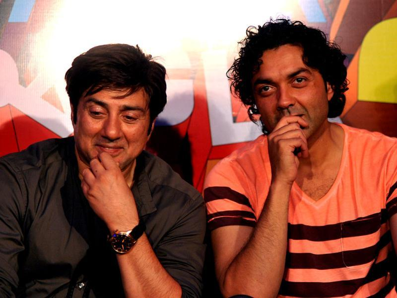 Sunny Deol (L) and Bobby Deol (R) look on during the launch of the forthcoming comedy 'Yamla Pagla Deewana 2' directed by Samir Karnikin Mumbai on March, 28 2013. (AFP PHOTO)