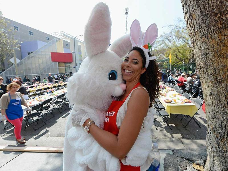Leslie Hughes with the reality television show 'The Bachelor' gets a hug from the Easter bunny as she volunteers to serve dinner during the Skid Row Easter event at the Los Angeles Mission in Los Angeles, California. (AFP Photo)