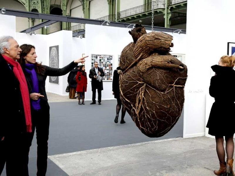 Visitors look at an artwork (C) by Russian artist Dimitri Tsykalov displayed during the opening of the