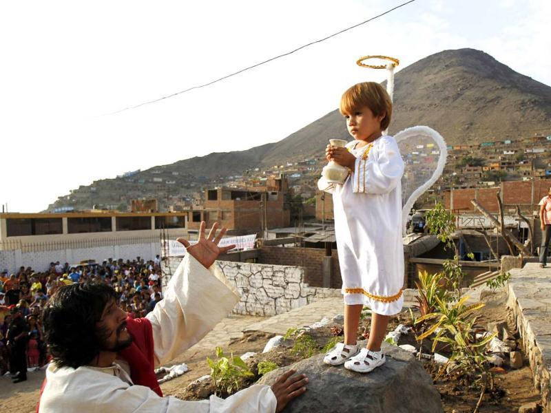 An actor playing the role of Jesus Christ gestures to a child during a re-enactment of the crucifixion of Jesus Christ on Good Friday in Comas. (Reuters)