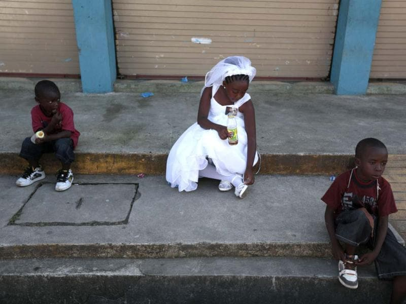 Children from the Garifuna ethnic people sit on a sidewalk during a re-enactment of the crucifixion of Jesus Christ on Good Friday during Holy Week in Livingston. (Reuters)