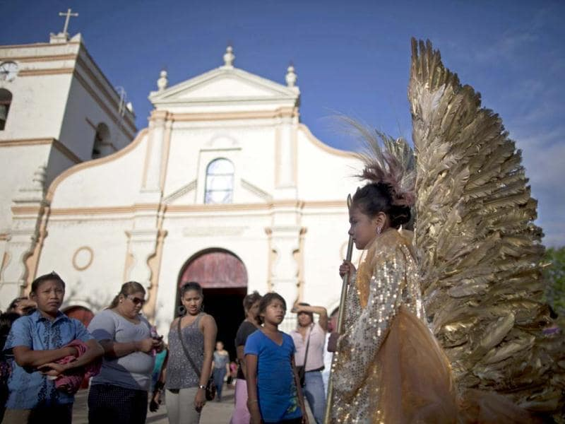 A girl wearing an angel costume wait for the start of a Good Friday procession in Masaya. (AP)