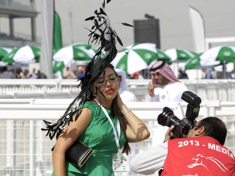 A woman poses for a photographer during the Dubai World Cup at the Meydan Racecourse in Dubai. (Reuters)