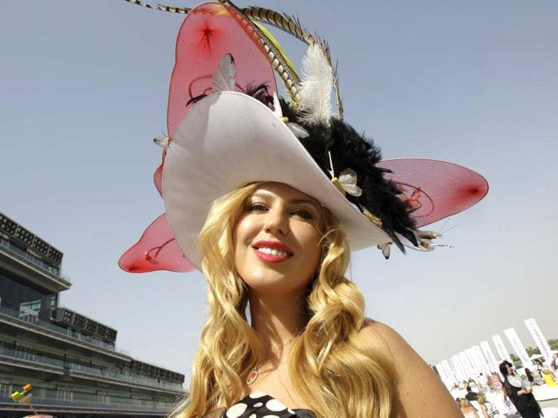 A woman poses for a photograph during the World Cup horse race at Meydan racecourse in Dubai, United Arab Emirates. (AP)
