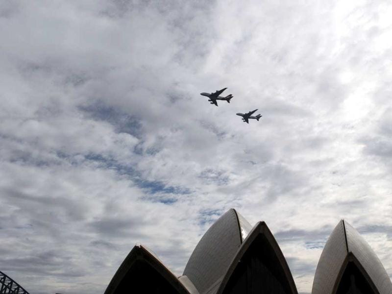 An Emirates A380 aircraft (below) and a Qantas A380 aircraft (top) fly over the Sydney Opera House to mark the official launch of the partnership between the two carriers. The spectacular tandem flyover of Sydney Harbour by the two super-jumbos is thought to be the first time anywhere in the world where two commercial airline A380's have flown in formation. (AFP Photo)