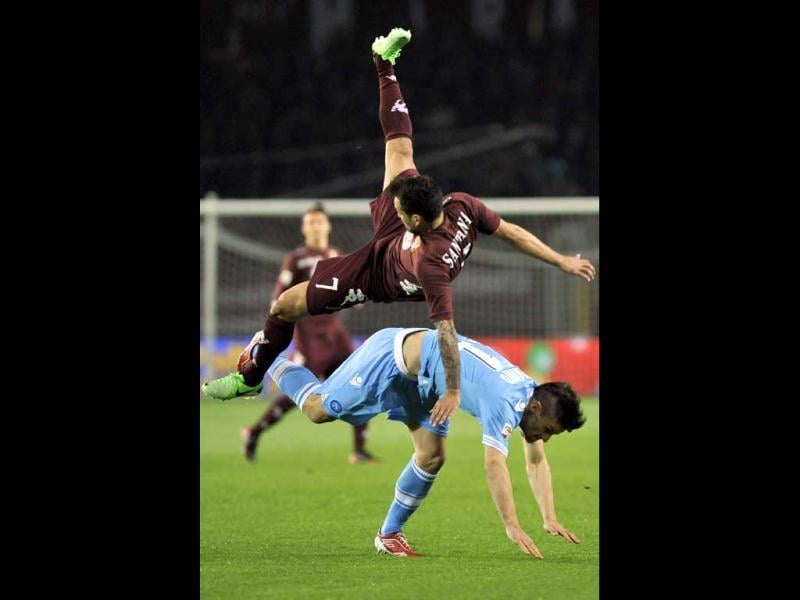 Torino's Mario Santana, of Argentina, top, is airborne as he challenges Napoli's Christian Maggio during a Serie A soccer match between Napoli and Torino, in Turin, Italy. (AP Photo)