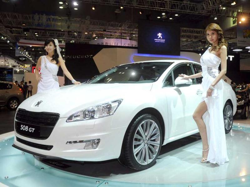 South Korean models pose with a Peugeot 508GT HDi car during a press preview of the Seoul Motor Show in Goyang, north of Seoul. (AFP Photo)
